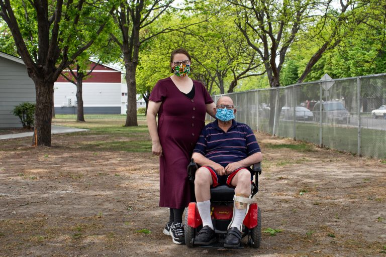 "Desirae Hernandez, a caregiver in Kennewick, Benton County, stands with her client Scott Philbeck, 60, at his apartment complex, April 29, 2020. ""It's been hard,"" says Philbeck, looking to Hernandez for suppport with expressing how things have been lately. ""He doesn't get out much these days and the anxiety from that can be debilitating I've noticed. The masks create this additional layer of claustrophobic anxiety for my clients as well."" (Matt M. McKnight/Crosscut)"