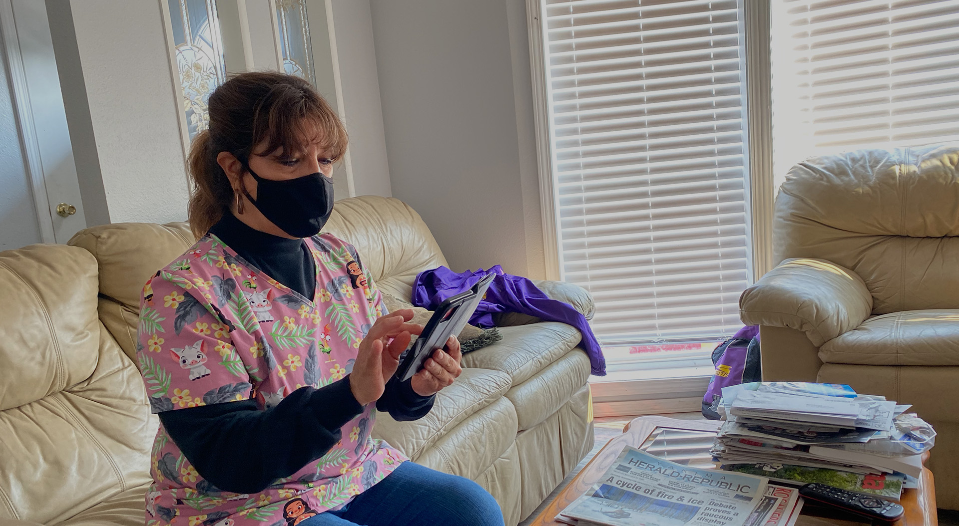 A caregiver wearing a mask looks at their phone