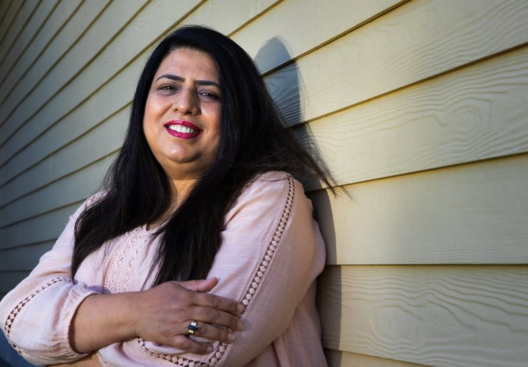 Shazia Anwar, a home care worker, stands in front of her Kent home Thursday. She has been caring for five clients throughout the coronavirus outbreak and works from 50-60 hours per week. (Ellen M. Banner / The Seattle Times)
