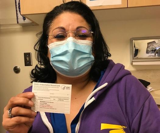 Caregiver shows vaccine card